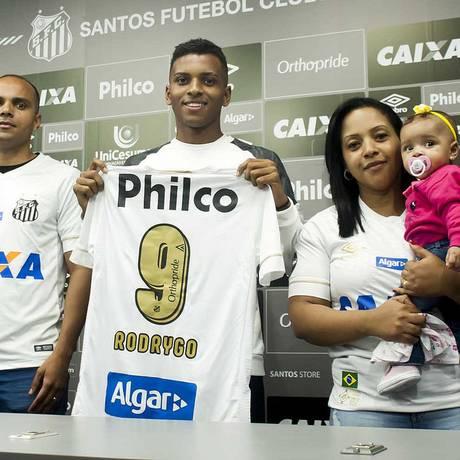 Rodrygo é presenteado pelos pais e pela irmã mais nova com a camisa 9 do Santos. A numeração dele passa a ser fixa por razões mercadológicas Foto: Ivan Storti / Santos FC