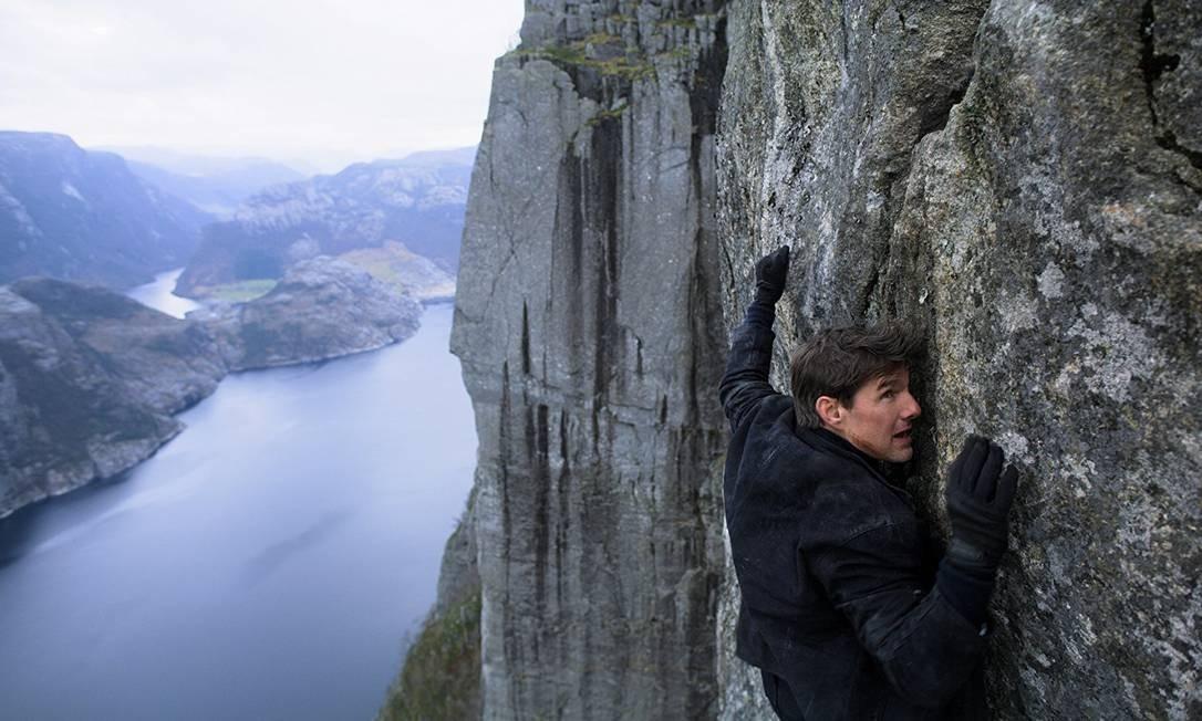 Tom Cruise se agarra ao paredão rochoso conhecido como Pedra do Púlpito, na Noruega, numa cena de