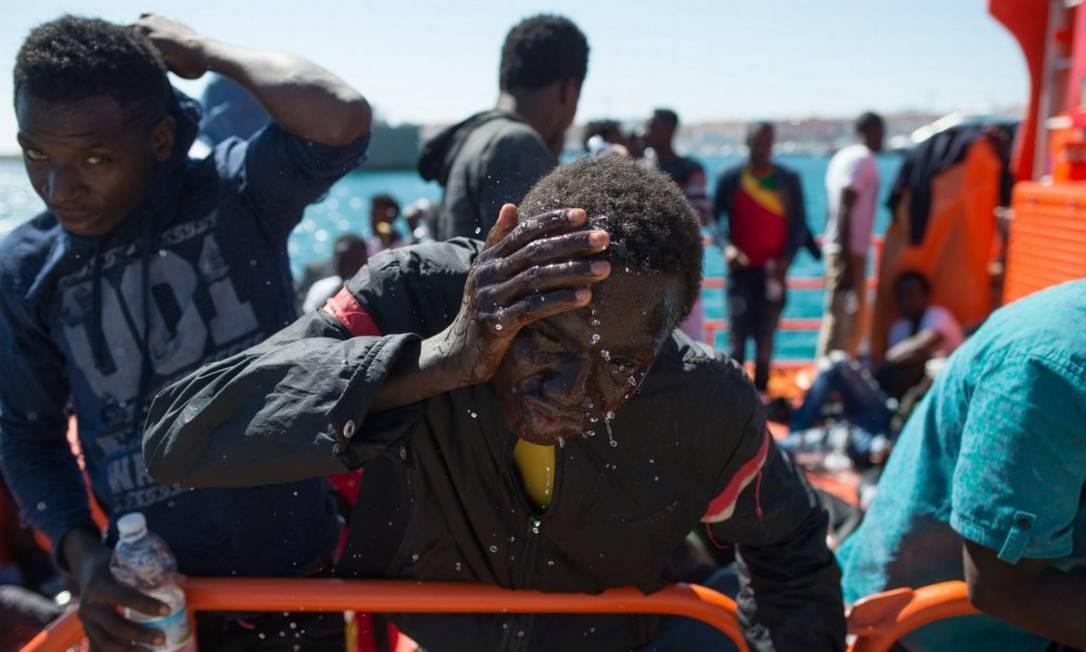 Imigrante se refresca após completar travessia pelo Mediterrâneo e desembarcar na costa da Espanha Foto: JORGE GUERRERO / AFP