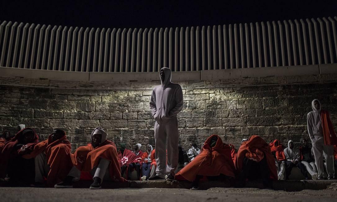 Imigrantes africanos são cobertos enquanto esperam processamento de solicitações de asilo no porto de Tarifa, na Espanha: desembarques disparam Foto: Olmo Calvo / Agência O Globo