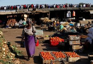 Mulher passa por feira aberta em Harare diante de evento por apoiadores da oposição Foto: SIPHIWE SIBEKO / REUTERS