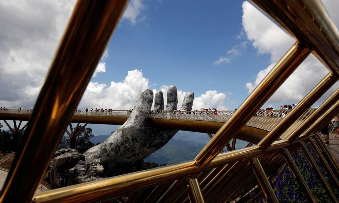 Visitantes caminham ao longo da bela Ponte Dourada Cau Vang, de 150 metros de comprimento, que fica em Ba Na Hills, perto de Danang, no Vietnã. A construção, no meio de florestas, tem duas mãos gigantescas de concreto que emergem das árvores, segurando a ponte dourada cintilante Foto: KHAM / REUTERS