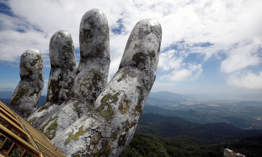 A mão, em detalhes, e a vista para a floresta vietnamita Foto: KHAM / REUTERS