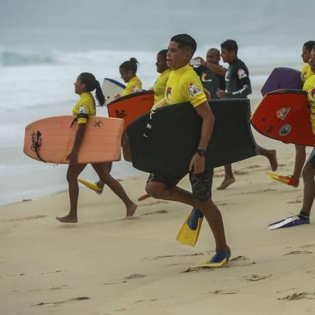 Alunos do projeto correm em direção à água observados pelos professores Foto: Marcelo Regua