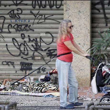 Sem perspectiva. Mulher passa com carrinho de bebê e cachorro próximo a jovem que dorme na calçada da Rua Barata Ribeiro, em Copacabana: Rio tem ao menos 4.628 moradores de rua, segundo último levantamento da prefeitura Foto: Domingos Peixoto / Agência O GLOBO