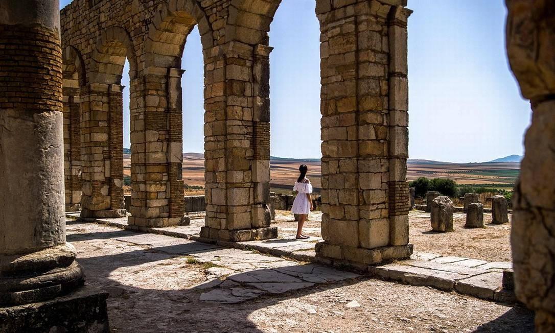 Turista caminha pelas ruínas da antiga cidade romana de Volubilis, perto de Moulay Idriss Zerhounon, no Marrocos FADEL SENNA / AFP