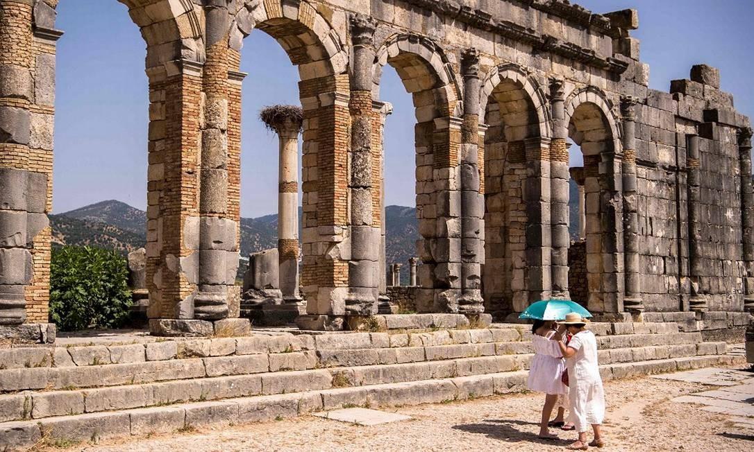 Touristas apelam para uma sombrinha para fugir do sol forte do norte da África durante visita às ruínas FADEL SENNA / AFP