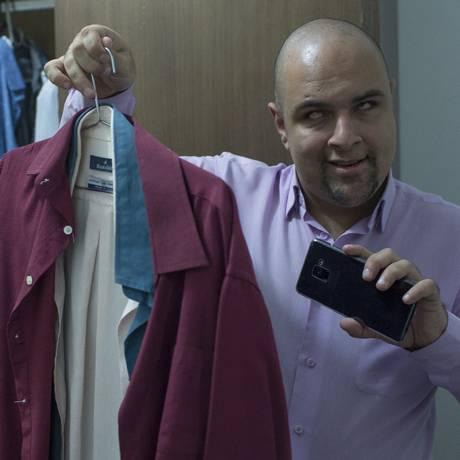 Com a ajuda de um voluntário pelo aplicativo de celular, Ton Oliver, que é cego, escolhe a cor da roupa que vai usar Foto: Edilson Dantas / Agência O Globo