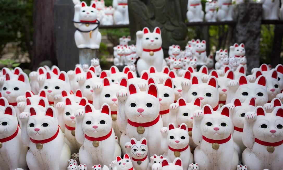 O templo de Gotokuji, em Tóquio, atrai visitantes com milhares de bonecos de gatos brancos que parecem trazer boa sorte. Foto: MARTIN BUREAU / AFP