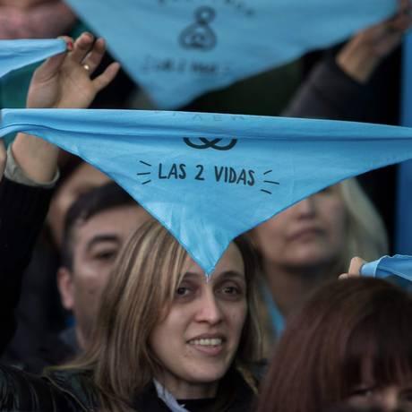 """Pessoas contrárias ao aborto seguram lenços azuis com o slogan """"as duas vidas"""" das campanha que pede a rejeição do projeto que legaliza a prática pelo Senado argentino no último sábado em Buenos Aires Foto: AFP/Alejandro Pagni"""