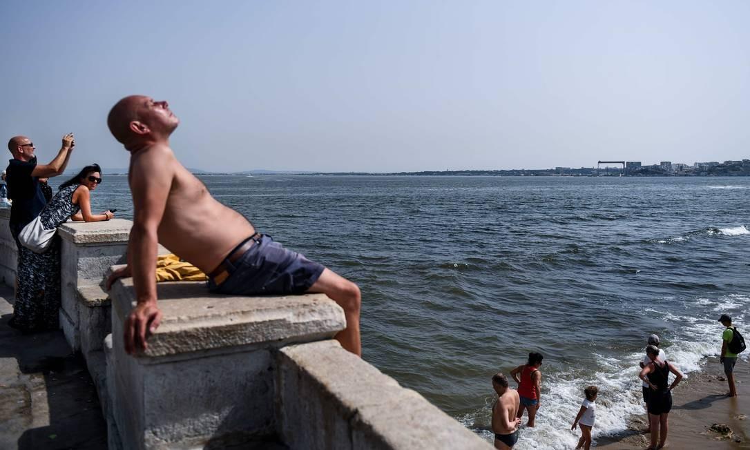 Portugueses e turistas se refrescam no Rio Tejo, na lisboeta Ribeira das Naus Foto: PATRICIA DE MELO MOREIRA / AFP