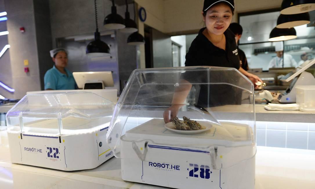 Na cozinha (ainda) trabalham seres humanos, que colocam os pratos nos robôs para serem entregues aos clientes ALBEE ZHANG / AFP