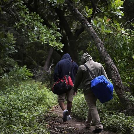 Os manifestantes nicaraguenses Guardabarranco e P.S.J. passam por um bosque a caminho do barco que os levaria para a Costa Rica Foto: MARVIN RECINOS / AFP