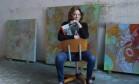 A artista plástica posa com seu livro, em seu ateliê em Nova York Foto: Divulgação