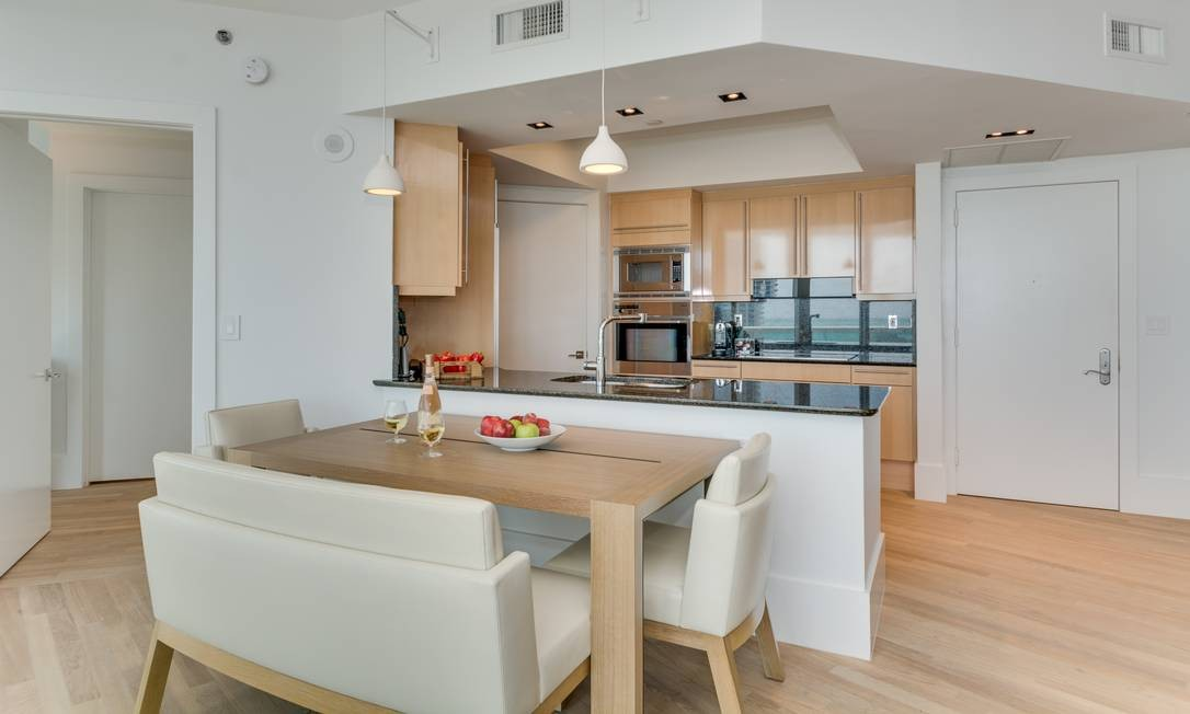 Neste apartamento em Miami, o arquiteto Mauricio Nóbrega usou o mesmo piso de madeira da sala à cozinha integrando totalmente os dois ambientes. Foto: Felipe Ariano / Divulgação