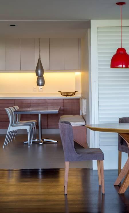 Neste apartamento, a cozinha é separada da sala de jantar por portas de venezianas brancas articuladas, que, quando abertas, permitem a integração total ou parcial dos dois ambientes. Foto: Divulgação / Divulgação