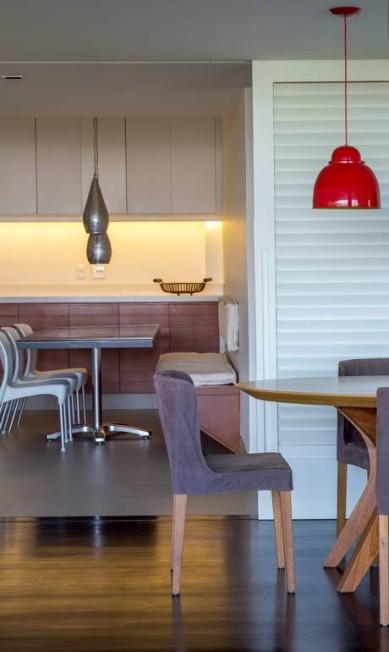 Neste apartamento, a cozinha é separada da sala de jantar por portas de venezianas brancas articuladas, que, quando abertas, permitem a integração total ou parcial dos dois ambientes. Divulgação / Divulgação