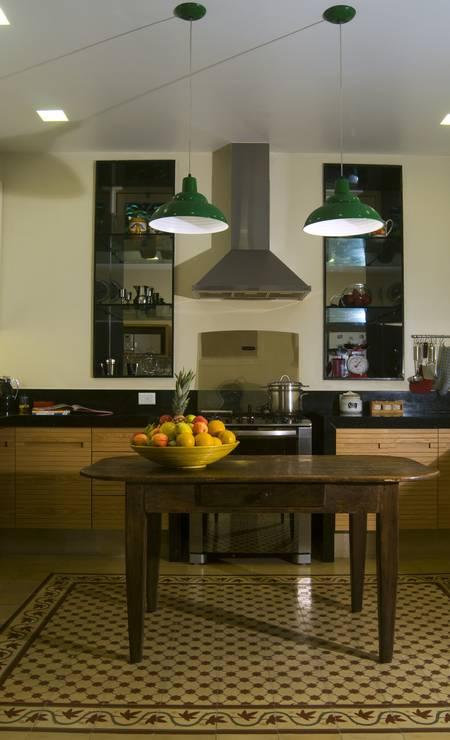 Dentro da cozinha, o ladrilho hidráulico usado como um tapete delimita o espaço da mesa antiga dando um ar aconchegante ao ambiente. Foto: Divulgação / Divulgação