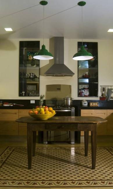 Dentro da cozinha, o ladrilho hidráulico usado como um tapete delimita o espaço da mesa antiga dando um ar aconchegante ao ambiente. Divulgação / Divulgação