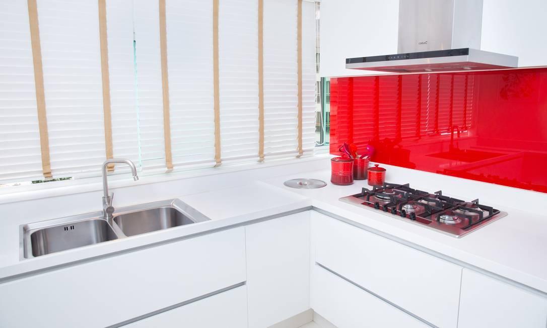 Esse apartamento em São Conrado, que têm grande incidência solar na cozinha, ganhou persianas de PVC (fáceis de limpar) nas janelas e um vidro pintado de vermelho na parede sob o fogão. A cor quebra o branco quase total do ambiente. E o vidro também facilita a limpeza. Foto: Divulgação / Divulgação