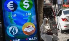 Uma mulher usa seu smartphone ao lado de um painel luminoso que mostra a cotação de moedas e da Bolsa da Turquia, em Istambul Foto: YASIN AKGUL / Yasin Akgul/AFP