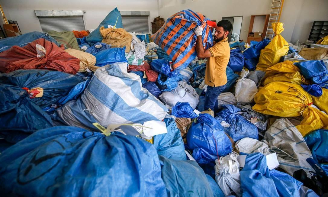 Carteiros palestinos organizam encomendas que ficaram retidas desde 2010 por autoridades israelenses Foto: ABBAS MOMANI / AFP