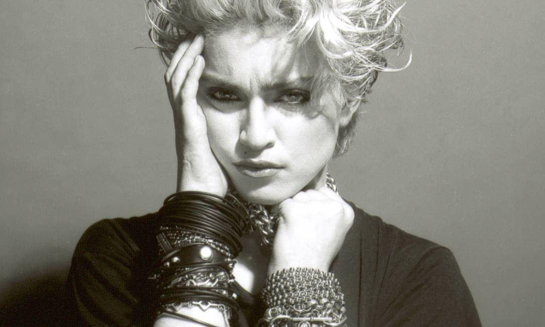 """Até chegar ao seu primeiro disco, Madonna já fazia e acontecia na cena cultural de Nova York e, obviamente, já havia transitado por muitos estilos. Mas achamos prudente começar a galeria que celebra os 60 anos da rainha do pop com a imagem que estampou a capa de seu primeiro disco intitulado... """"Madonna"""" (1983). A partir daquele momento, olhos marcados, pulseiras """"empilhadas"""" e cabelos platinados virariam febre mundial Foto: Divulgação"""