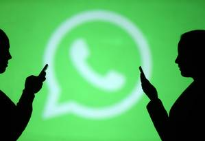 Silhouettes of mobile users are seen next to a screen projection of Whatsapp logo in this picture illustration taken March 28, 2018. REUTERS/Dado Ruvic Foto: DADO RUVIC / Reuters