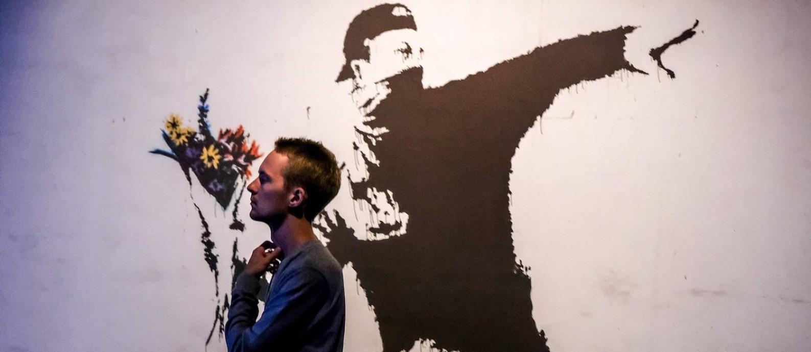 Visitante na exposição de obras de Banksy em Moscou Foto: YURI KADOBNOV / AFP