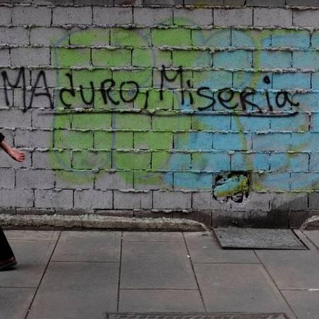 Venezuelanos caminham em frente a muro com os dizeres