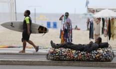 Descanso. Depois de andar por cerca de 40 quilômetros, Sérgio descansa na orla de Copacabana sobre as latinhas que catou: ele ganha R$ 70 por dia Foto: Domingos Peixoto