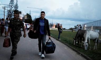 Um refugiado venezuelano recebe ajuda de um militar brasileiro após receber passagem para Foz do Iguaçu Foto: Nacho Doce / Reuters