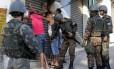 Os militares revistam um grupo de pessoas Foto: Marcos de Paula / Agência O Globo
