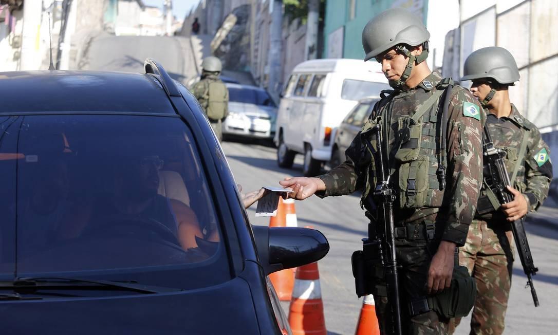 Militares olham documento de motorista no Complexo do Alemão Foto: Marcos de Paula / Agência O Globo