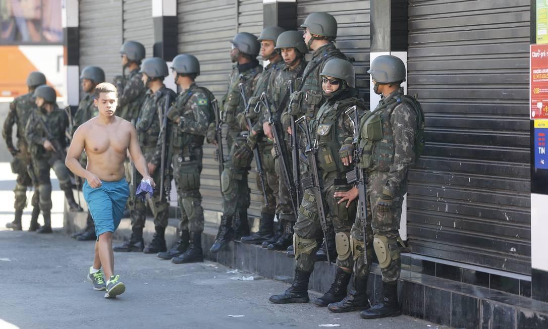 Morador do Complexo da Maré passa por militares que estavam em operação na comunidade Foto: Pablo Jacob / Agência O Globo