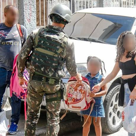 Um militar revista a mochila de uma criança no Alemão Foto: Bruno Itan / Olhar Complexo