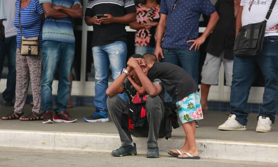 O marido de Vânia, Carlos Alberto Lopes, é consolado pelo filho em frente ao Hospital municipal Moacyr do Carmo, em Duque de Caxias Foto: Brenno Carvalho / Agência O Globo