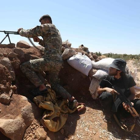 Combatentes rebeldes durante confronto direto na província de Idlib, bastião de resistência contra o governo de Damasco Foto: OMAR HAJ KADOUR / AFP