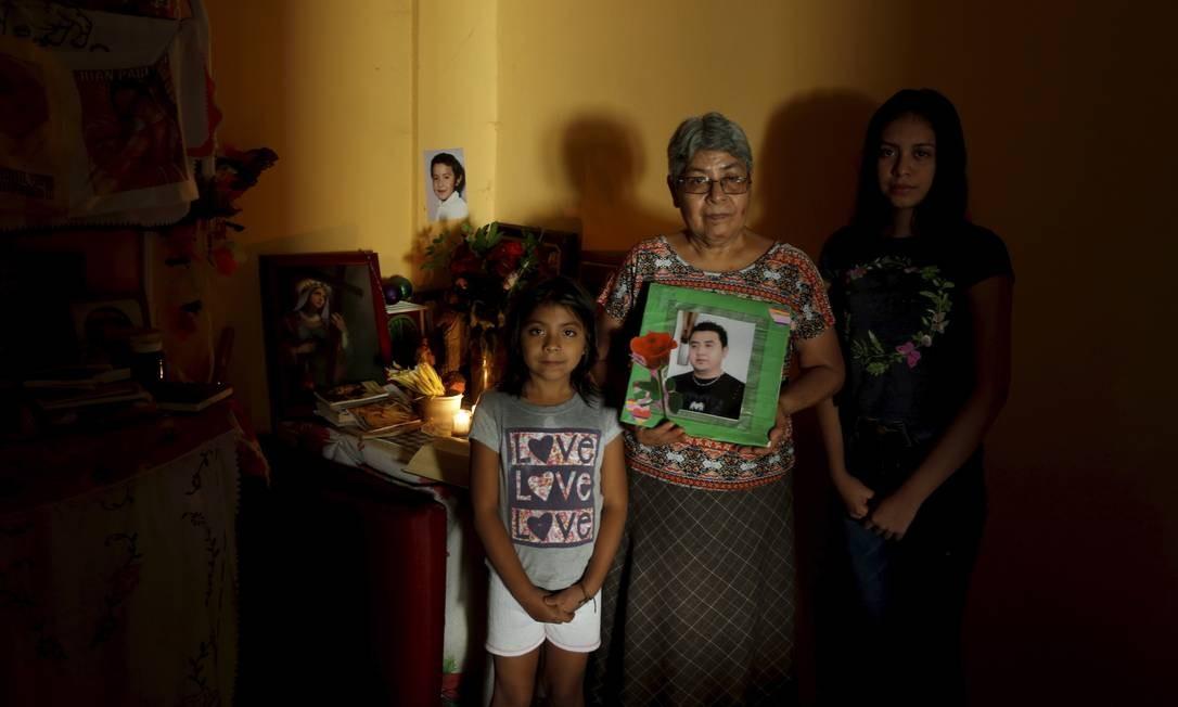 Guadalupe Casarubias com suas netas mostra a foto de seu filho Pedro sequestrado no dia 27/10/2012 dentro de seu trabalho Foto: Domingos Peixoto / Agência O Globo