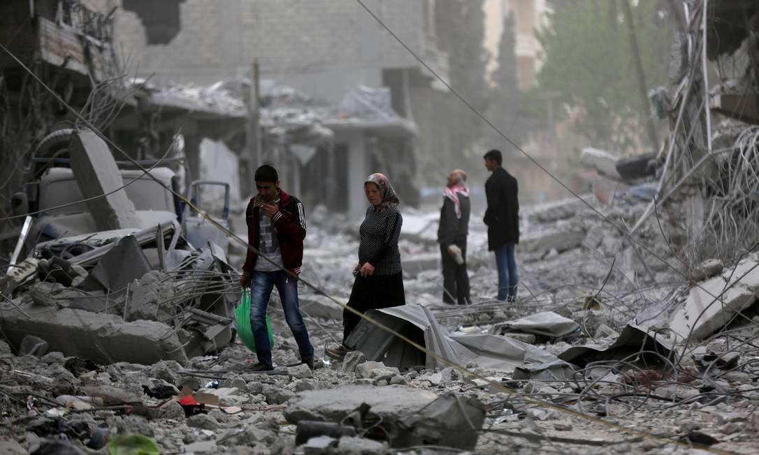Civis andam sobre os destroços na cidade de Afrin, na Síria, vítima de ataques Foto: Khalil Ashawi / REUTERS