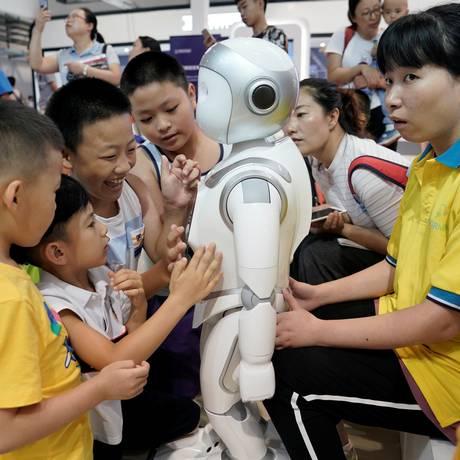 Crianças brincam com robô no estande da AvatarMind na World Robot Conference Foto: JASON LEE / REUTERS