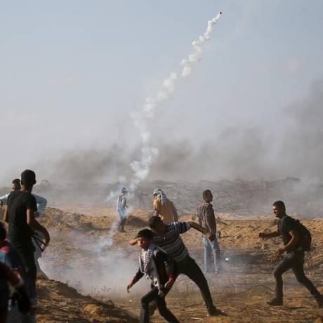 Palestinos tentam se desviar de bombas de gás lacrimogêneo lançadas por Israel na Faixa de Gaza Foto: Ibraheem Abu Mustafa / REUTERS