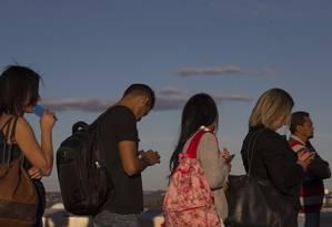 A espera de transporte, todas as pessoas conectadas ao smartphone, em Brasília: projeto de lei quer quer aparelhos celulares têm alerta de risco do uso para a coluna cervical Foto: Daniel Marenco/24-07-2018