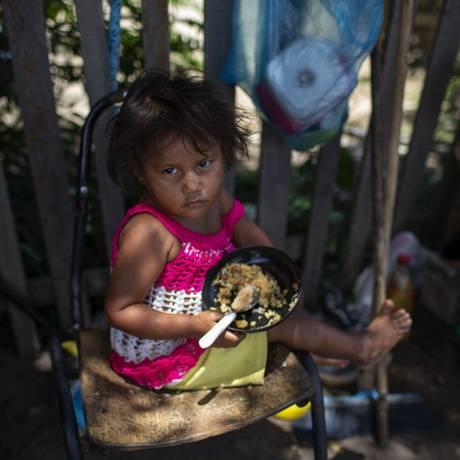 A pequena venezuelana Alejandra, de dois anos, come na beira da estrada em Boa Vista, no estado brasileiro de Roraima Foto: MAURO PIMENTEL / AFP