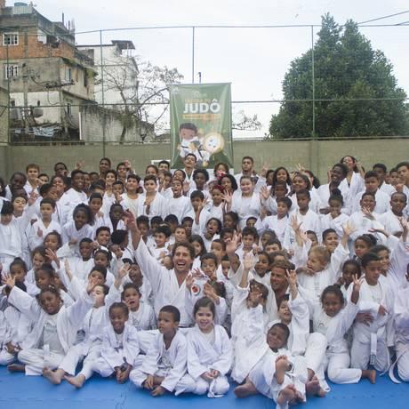 O medalhista olímpico Flávio Canto com alunos da Ong Solar Meninos de Luz, no Pavão Pavãozinho Foto: Divulgação