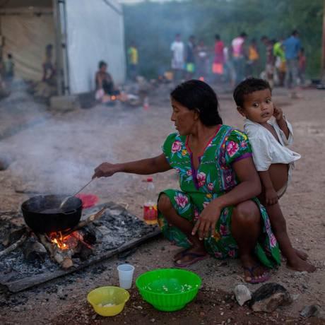 Índios da etnia warao preparam sua própria comida em abrigo de Pacaraima, no estado brasileiro de Roraima Foto: MAURO PIMENTEL / AFP