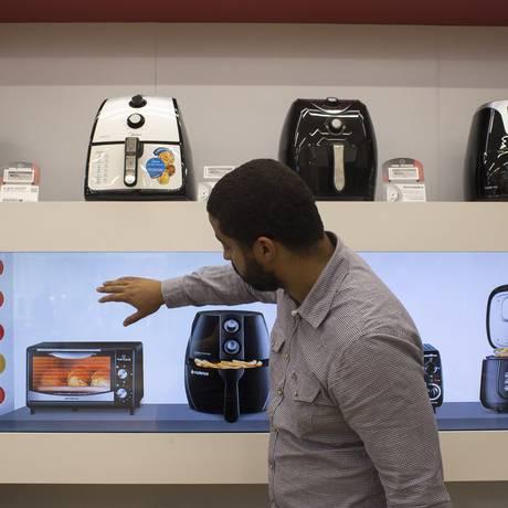 Tela na vitrine. Cliente escolhe produtos em prateleira virtual de loja do Pontofrio em shopping de São Paulo: mais chance de vender com portfólio ampliado Foto: Edilson Dantas / O Globo