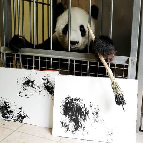 A fêmea de urso panda Yang Yang aprendeu a usar um pincel para pintar Foto: HEINZ-PETER BADER / REUTERS