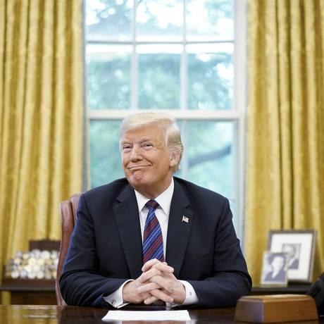 Donald Trump sorri durante uma conversa telefônica com o presidente do México, Enrique Pena Nieto, sobre o acordo de comércio entre os dois países, no Salão Oval da Casa Branca Foto: MANDEL NGAN / AFP