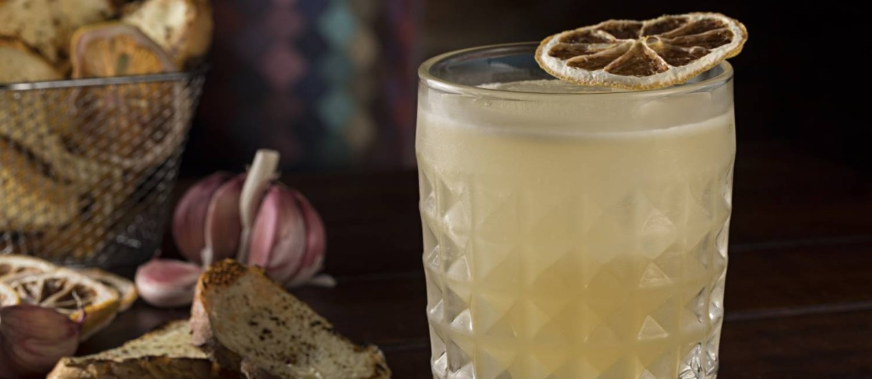 Drinque muquirana, do Garoa. Servido com torradinhas no estilo pão de alho, ele leva cachaça, xarope de mel e limão. Foto: Rodrigo Azevedo